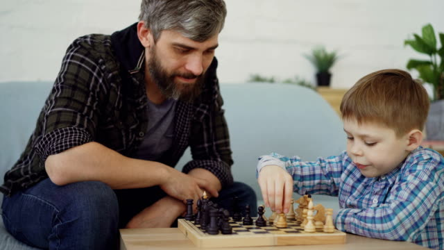 Clever small boy is playing chess with his caring father touching chesspieces and moving chessmen. Intellectual game, happy family and generations concept. Clever small boy is playing chess with his caring father touching chesspieces and moving chessmen at home. Intellectual game, happy family and generations concept. plank timber stock videos & royalty-free footage