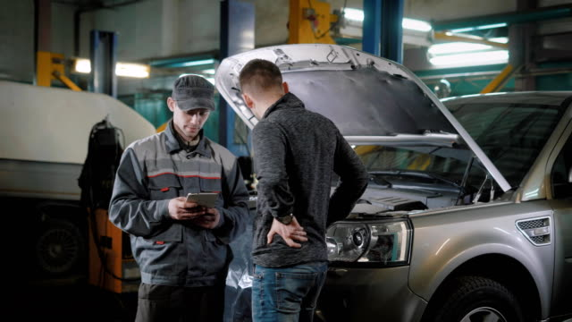 Client and car mechanic standing near car video