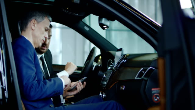 Client and dealer connecting smartphone to car Side view of manager and businessman connecting smartphone to car computer in showroom. salesman stock videos & royalty-free footage