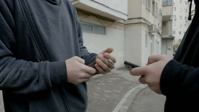 Client buying cocaine drugs at the corner of the street from a drug dealer who accepts bitcoin cryptocurrency payment from smartphone video