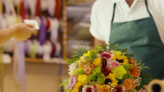 client paying florist in flower shop with credit card video