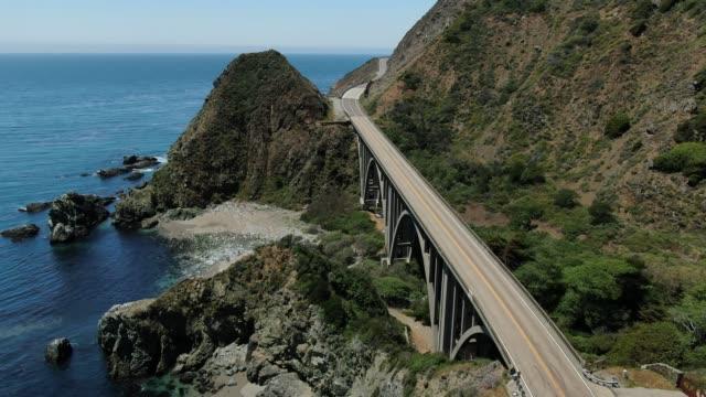vídeos de stock e filmes b-roll de cliff coastal iconic bridge aerial - estrada 001