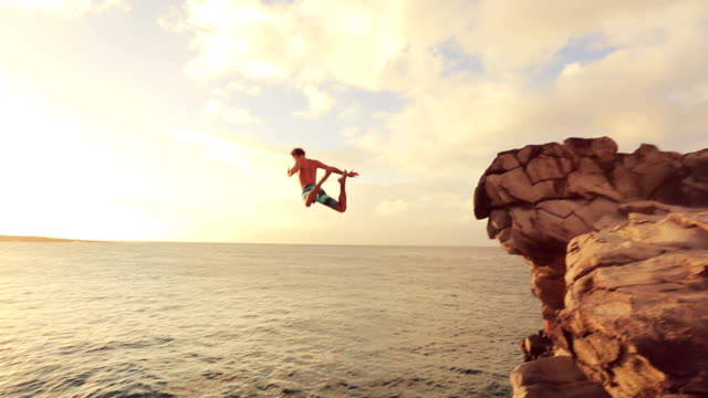 cliff jumping at sunset. summer extreme sports cliff jumping outdoor lifestyle - cliffs stock videos & royalty-free footage