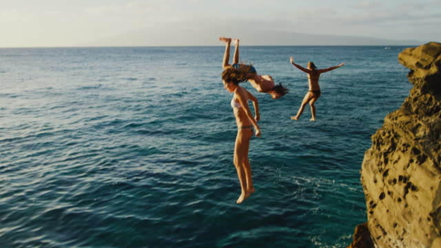 Cliff Jumping at Sunset Friends cliff jumping into the ocean at sunset bolos stock videos & royalty-free footage