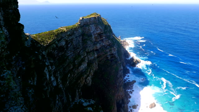 Cliff side of Cape Point in Cape Peninsula Beautiful shot of a coastline at (Cape Point in Cape Peninsula) in South Africa. In the background endless sea of ocean with waves crashing on to the island. This is still part of Table Mountain in Cape Town. south stock videos & royalty-free footage