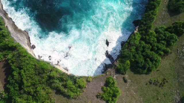 cliff med vågorna kraschar mot en stenig strand, nusa penida, indonesien. - zoom ut bildbanksvideor och videomaterial från bakom kulisserna