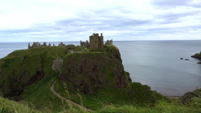 vídeos de stock, filmes e b-roll de falésias e castelo na costa da escócia - castelo