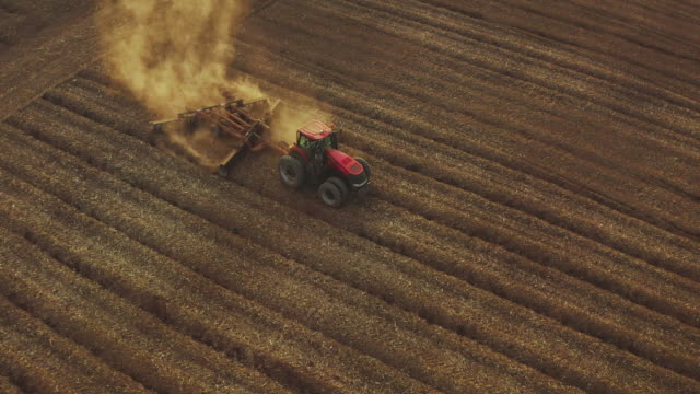 Climate change drought Aerial view of a farmer driving a red tractor through dusty fields at sunset with golden dirt rising into the air, farming at sunset, climate change barren dusty fields plow stock videos & royalty-free footage