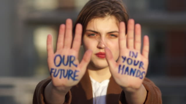 vídeos de stock e filmes b-roll de climatic strike. close portrait of a short-haired girl. the student holds her hands in front of her, the inscription on them - our future is in your hands - green world