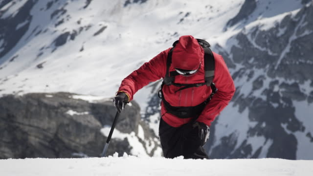 Climber arrives at a snow-covered mountain peak video