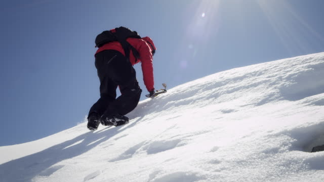 Climber arrives at the snow-covered mountain peak video
