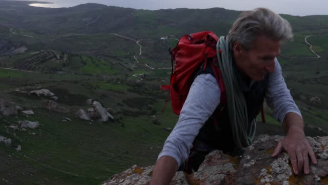 Climber ascends steep cliff above sea, hills video