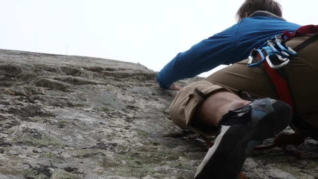 Climber ascends steep cliff into fog video