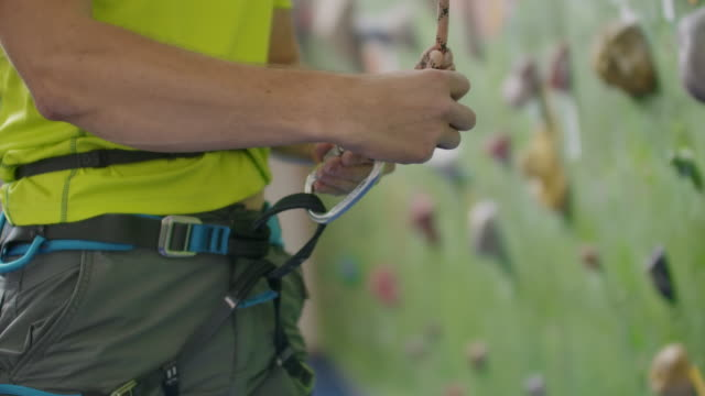 Climber attaching a belay rope and Chalking hands