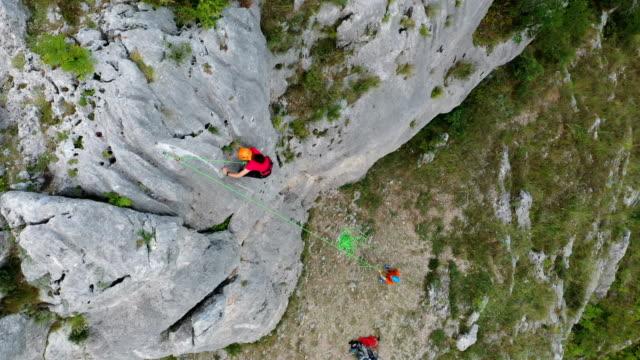 vidéos et rushes de grimpeur grimpant sur un rocher, travail d'équipe - paysage extrême