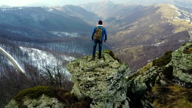 climber enjoys the view from the top of the mountain - in cima video stock e b–roll