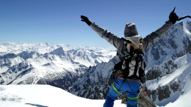 Climber mountaineer man reaching snowy mount top success in sunny day.Mountaineering ski activity. Skier people winter snow sport in alpine mountain outdoor.Back view.Slow motion 60p 4k video