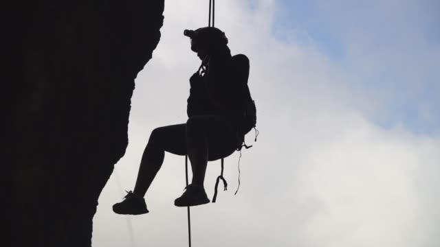 Climber silhouette descending the rock by rope at sky background video