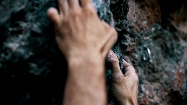 climber trying to climb up the rock - inerpicarsi video stock e b–roll