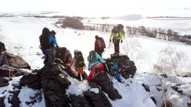 climbers, a friendly team, go through a mountain cliff. aerial - mountain top filmów i materiałów b-roll