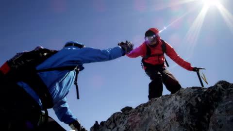 vidéos et rushes de les grimpeurs sont en s'entraidant sur les rochers sur la montagne - assistant