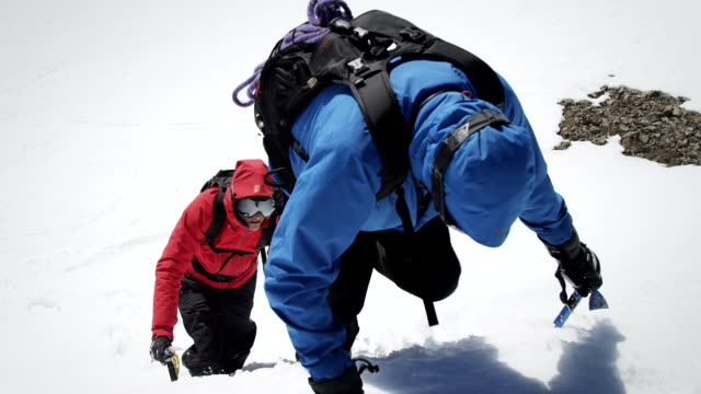 Climbers arrive at the snow-covered mountain peak video