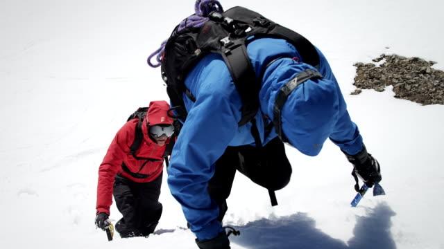 vídeos de stock e filmes b-roll de alpinistas chegar ao cume da montanha coberta de neve - equipa desportiva