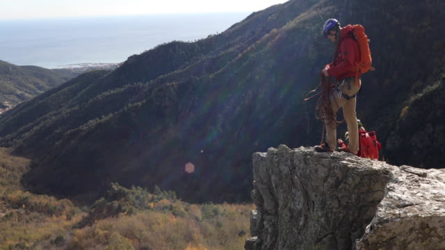 Climbers ascend rock ridge crest above valley, sea They arrange gear before setting out pedal pushers stock videos & royalty-free footage