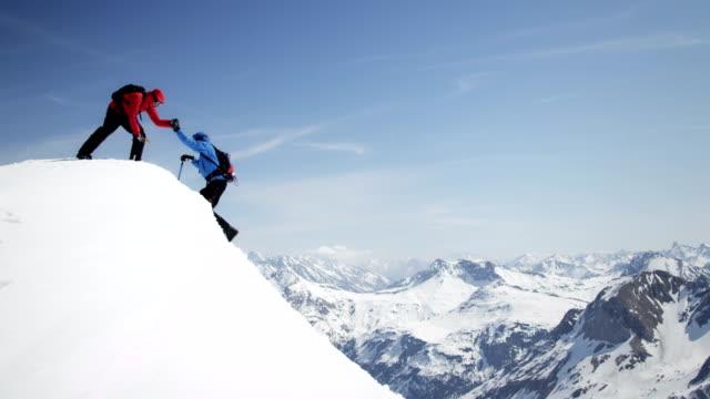 альпинисты, помогая друг другу прибыть в снежные пик - альпинизм стоковые видео и кадры b-roll