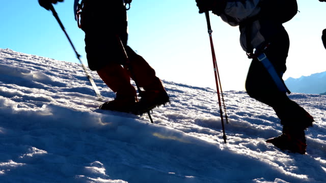 climbers in crampons coming up to the summit of elbrus. silhouette over extremely exposed area - альпинизм стоковые видео и кадры b-roll