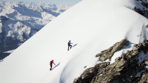 Climbers on a snow-covered mountain Extrem long shot of two climbers on a snow-covered mountain during sunshine. The climbers climb one after another along the mountain. Camera moves around the mountain. Some other mountains are seen in the background. mountain stock videos & royalty-free footage