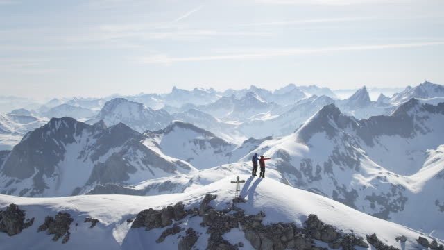 Climbers standing on a snow-covered mountain peak video