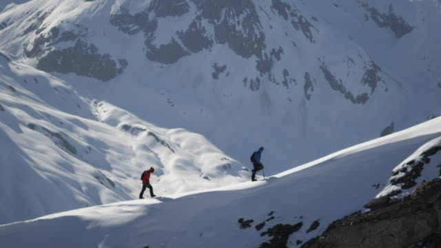 Climbers walk on a snow-covered mountain video