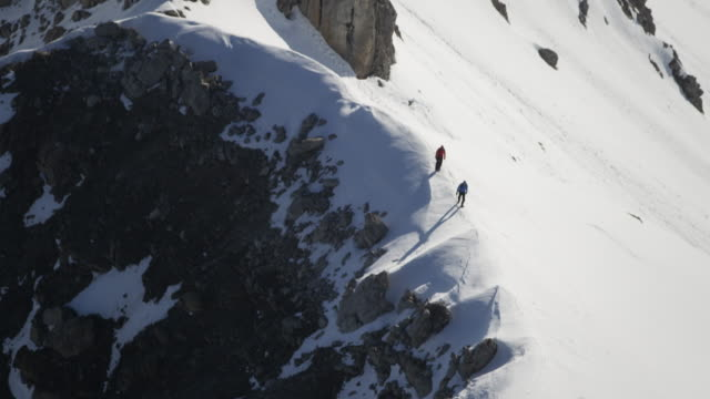 Climbers walk on the top of a snow-covered mountain