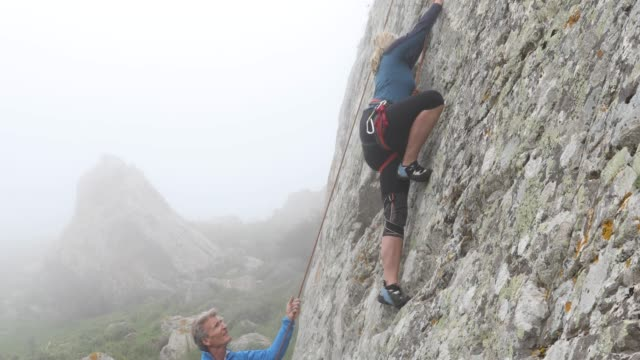 climbing couple ascend rock cliff in foggy condistions - pantaloni capri video stock e b–roll