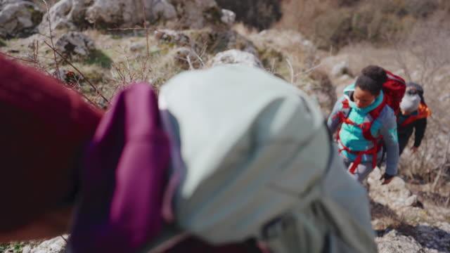 Climbing learners following their climbing instructor in rough terrain