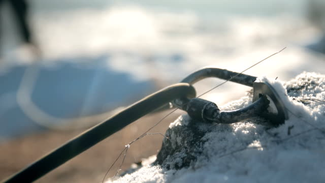 climbing rope slides in a carabiner. insurance climbers closeup. - альпинизм стоковые видео и кадры b-roll