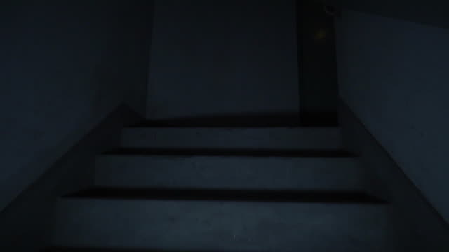 Climbing spooky stairs in darkness.