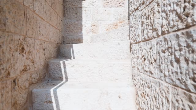 Climbing the ancient stone stairs in the maze of the streets of the old city of Jerusalem, Israel. Stone Tunnel with steps in sunny day.