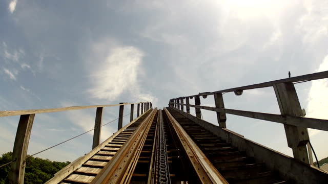 climbing to the top of a classic wooden roller coaste - luna park video stock e b–roll