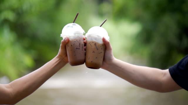 vídeos de stock, filmes e b-roll de vidros do clink do chocolate frio e do café gelado na natureza no movimento lento - chocolate quente