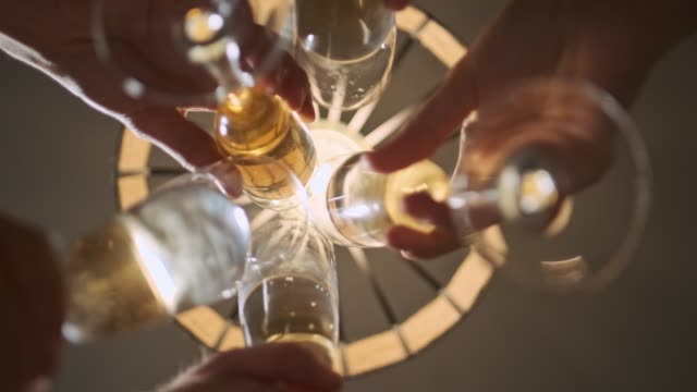 vidéos et rushes de verres de champagne clignotants. toast célébrant noel. lumières jaunes sur l'arrière-plan. beaucoup de mains. un groupe d'amis. - champagne