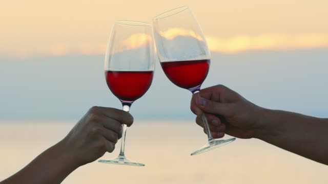 SLO MO Clinking red wine glasses by the sea at sunset