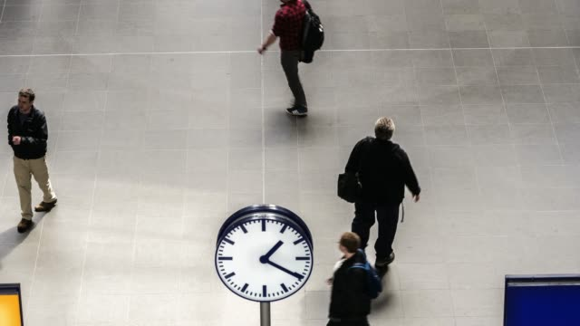 Clock and travellers in station timelapse of travellers, in the front ground a clock in focus at Haubtbahnhof, Berlin, Germany subway station stock videos & royalty-free footage