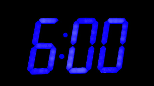LED clock display with large blue numbers, working with blinking seconds, changes one hour to another.