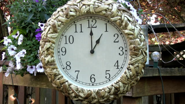 Clock outdoors on patio deck set to 1PM video