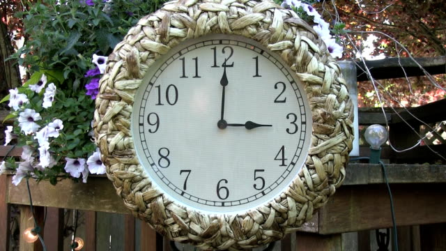 Clock outdoors on patio deck set to 3PM video