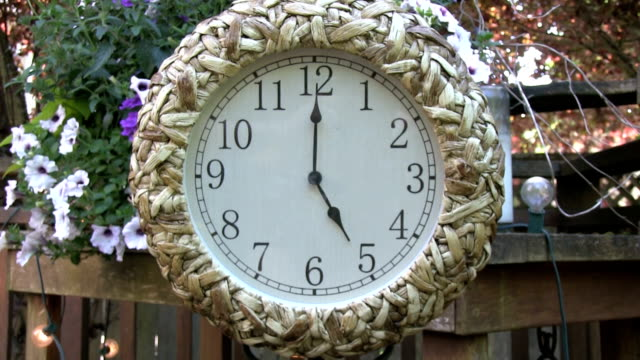 Clock outdoors on patio deck set to 5PM Rack Focus video