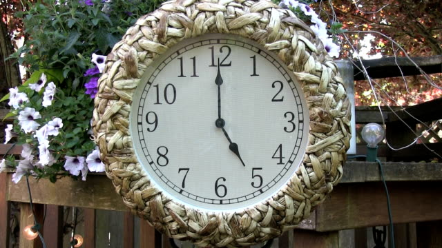 Clock outdoors on patio deck set to 5PM video