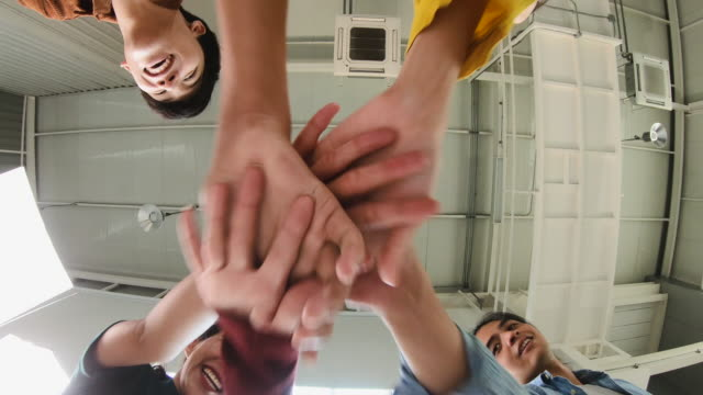Cloese up looking directly below stacking hand of creative coworker and raising hand for celebration success